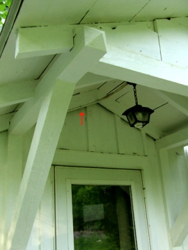 The Guest House portico where I watched a phoebe nest; the arrow points to the location of a bat which also chose to nest under the roof another time