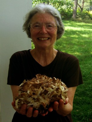 Holding a maitake, also known as a hen-of-the-woods mushroom